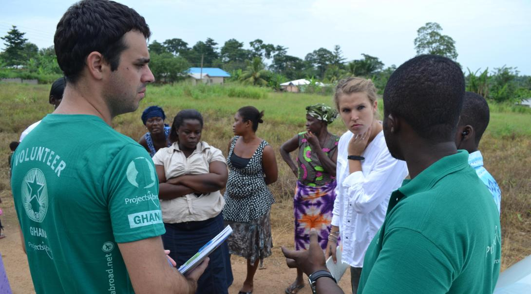 A couple of Projects Abroad volunteers discuss some solutions to a local problem with staff and local women in Ghana during their social work internship.